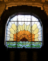 Daylight streams through a big stained window at one end of the lobby.